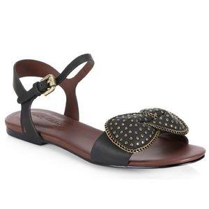{ Chloe } Clara Flat Studded Bow Sandals in Black